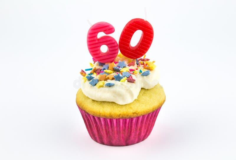 Muffin med rosa färgstearinljus för nummer sextio - 60 - med vit vanilj arkivbild