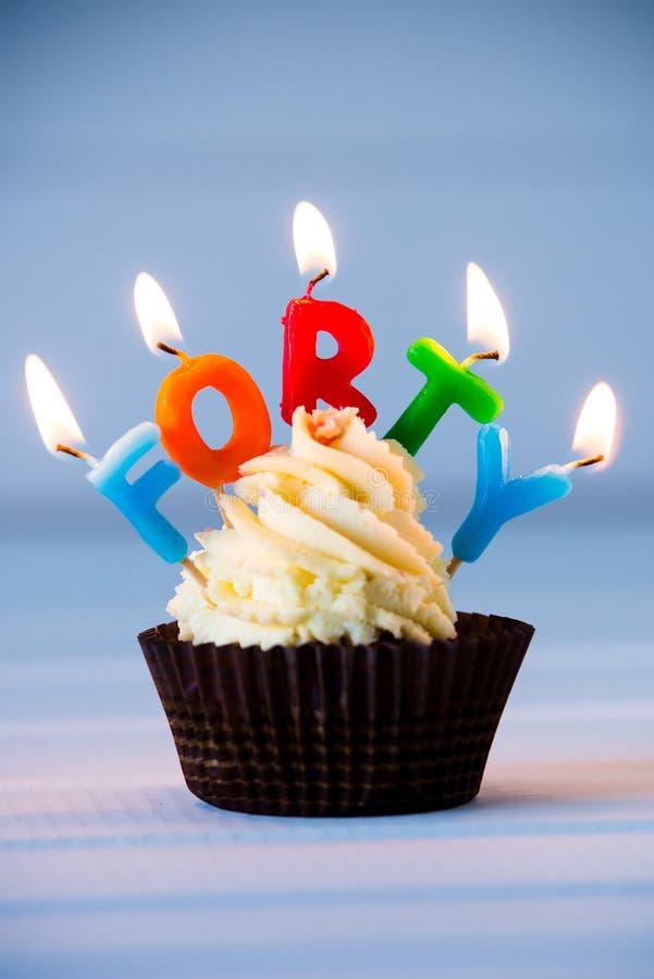 Muffin med stearinljus för 40 - fyrtionde födelsedag lycklig födelsedag royaltyfria bilder