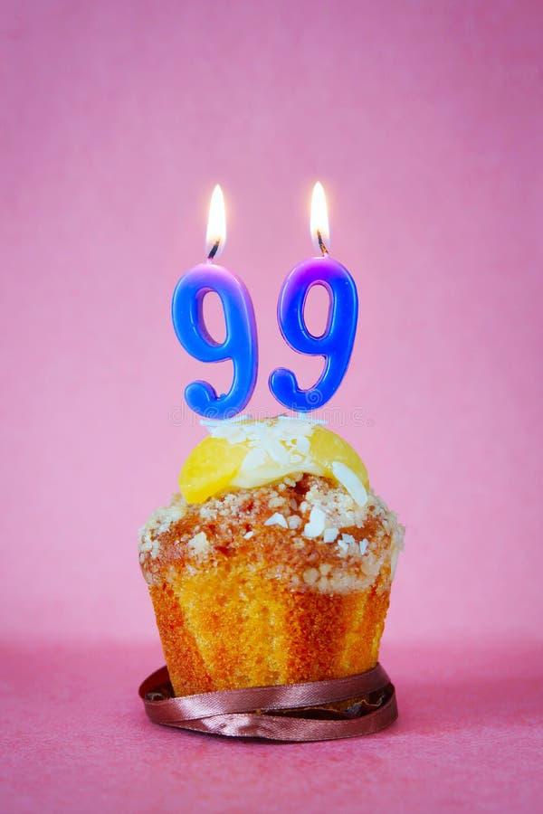 Muffin met het branden van verjaardagskaarsen als nummer negenennegentig stock foto's