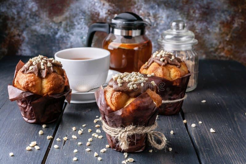 Muffin met melkchocola en noten, op smaak gebrachte oranje thee op houten achtergrond royalty-vrije stock afbeelding
