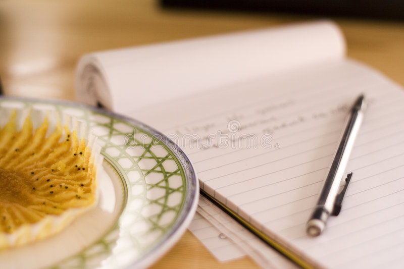 Muffin and Notepad. Taking quick notes during breakfast royalty free stock photo