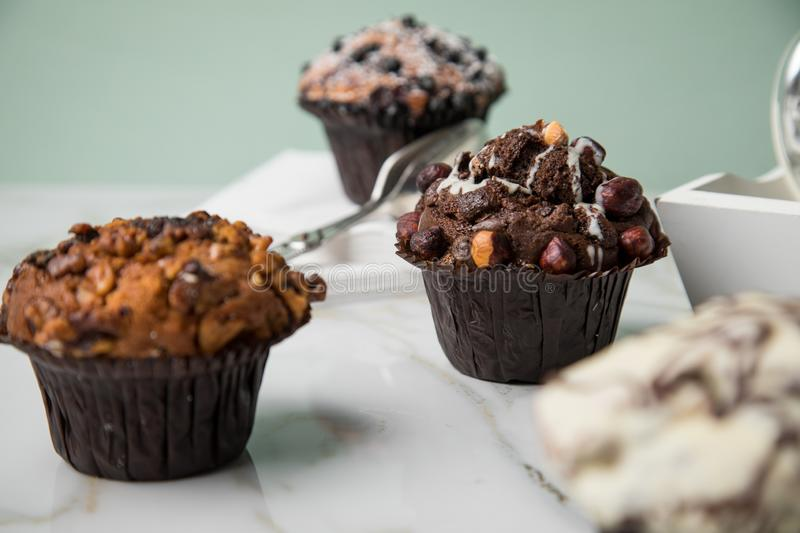 Muffin selection with blueberry, walnuts, hazelnuts and white chocolate for coffee break on marble table and green background royalty free stock images