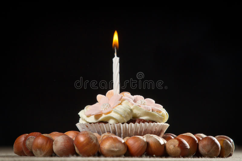 Muffin with small burning candle royalty free stock photos