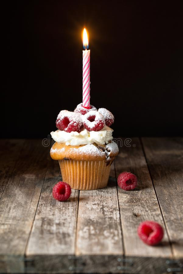 Muffin with soft cream and fresh raspberry powdered with sugar and decorated with burning candle, happy birthday card, rustic stock photo