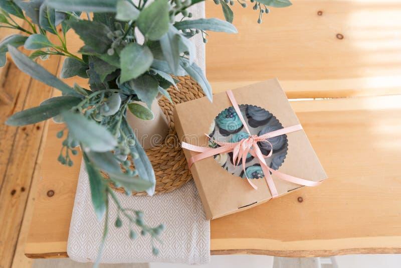 Muffin som förpackar på trätabellen, leveransask, vaniljmuffin med blå och vit kräm B?sta sikt, kopieringsutrymme arkivfoto