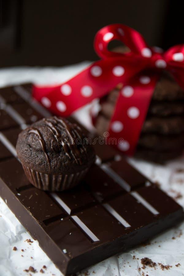 Muffin- und Schokoladensplitterplätzchen mit Schokoriegel und roter silk Bogen mit weißen Punkten stockfotos