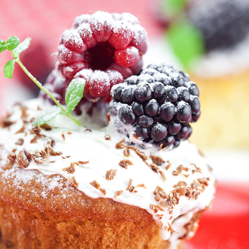 Muffin with whipped cream and cake with icing