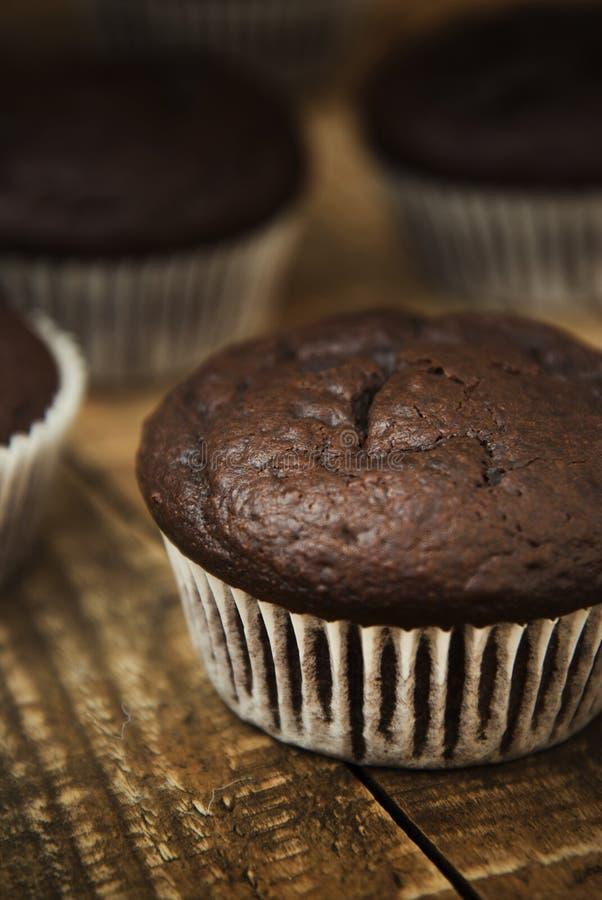 Muffiner med chokladefterrätten Hemlagade chokladmuffin med kryddor på träbakgrund söt efterrätt Mörkt foto tonat royaltyfri foto