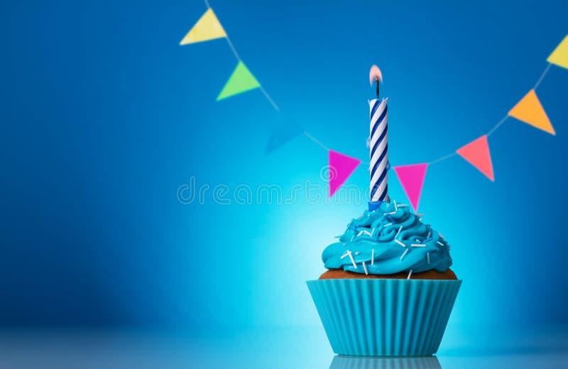 Muffinfödelsedag med den härliga stearinljuset på ljus blå bakgrund royaltyfri fotografi