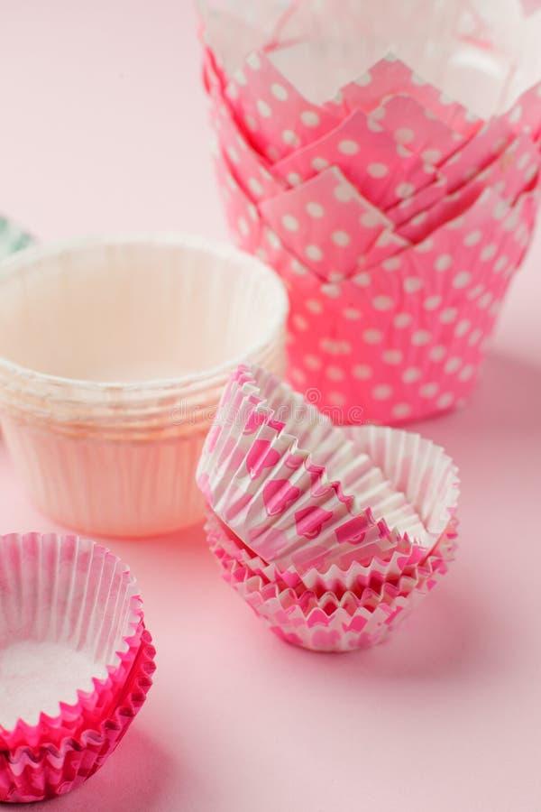 Muffinfall står högt i variation av färg och formatet på den rosa tabellen som är klar för ferieberöm och att baka begrepp royaltyfri fotografi