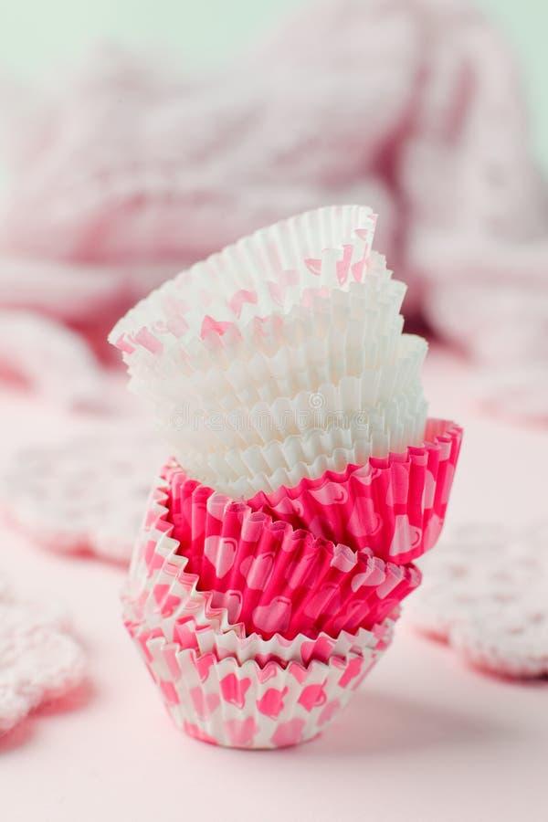 Muffinfall står högt i variation av färg och formatet på den rosa tabellen som är klar för ferieberöm och att baka begrepp Papper fotografering för bildbyråer