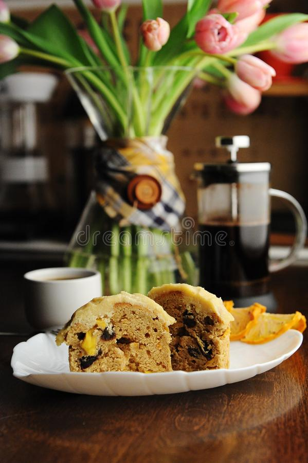 Muffinkuchen mit kandierter Frucht und Eifer auf wei?er Platte Franzose-Presse-Kaffee Rosa Tulpen im Dekantiergef?? lizenzfreie stockfotografie