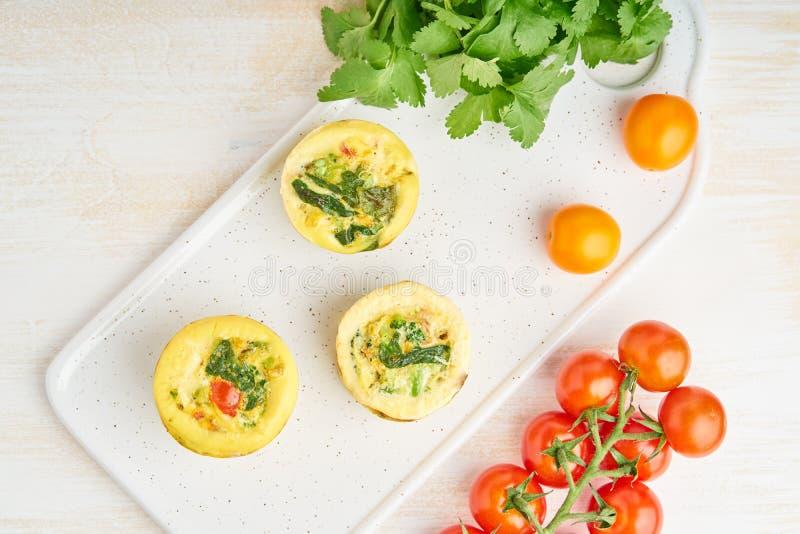 Muffins αυγών, paleo, keto διατροφή Ομελέτα με το σπανάκι, λαχανικά, ντομάτες που ψήνονται στις μικρές φόρμες, τοπ άποψη στοκ εικόνα με δικαίωμα ελεύθερης χρήσης