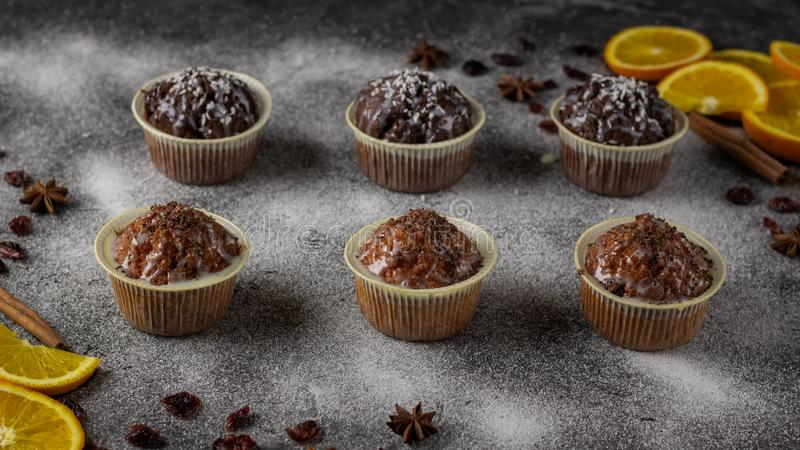 Muffins και πορτοκάλια για το επιδόρπιο Υπόβαθρο γκρίζο από την κονιοποιημένη ζάχαρη στοκ εικόνες