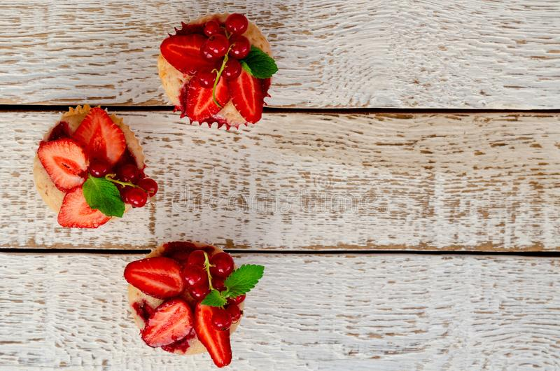 Muffins κινηματογραφήσεων σε πρώτο πλάνο διακόσμησαν τη φρέσκια φράουλα στο παλαιό άσπρο ξύλινο επιτραπέζιο υπόβαθρο στοκ εικόνα με δικαίωμα ελεύθερης χρήσης