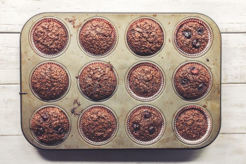 Muffins πίτουρου σοκολάτας με τα κεράσια, σε παλαιό, grunge κοιτάζοντας, δίσκος κασσίτερου στοκ φωτογραφίες