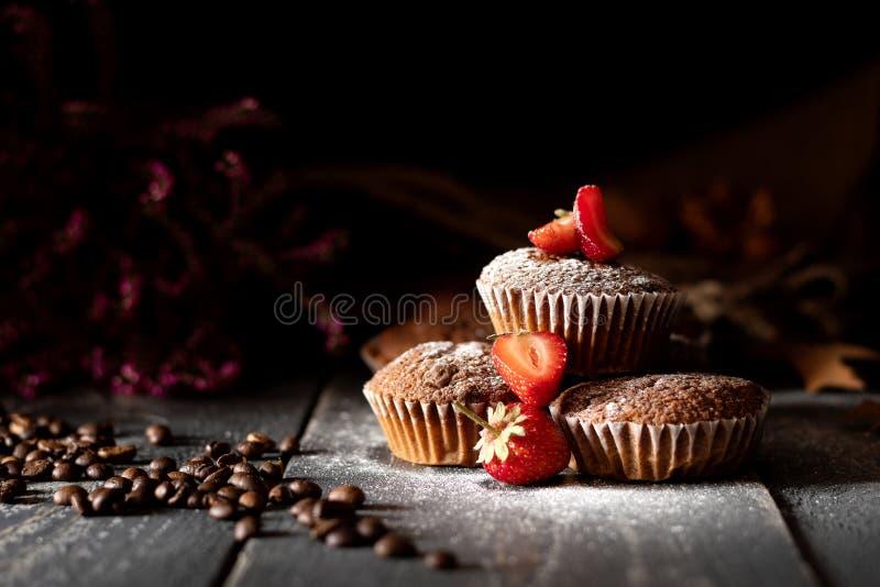 Muffins σοκολάτας με τις φράουλες και καφές που ψεκάζεται με την κονιοποιημένη ζάχαρη στοκ εικόνα με δικαίωμα ελεύθερης χρήσης
