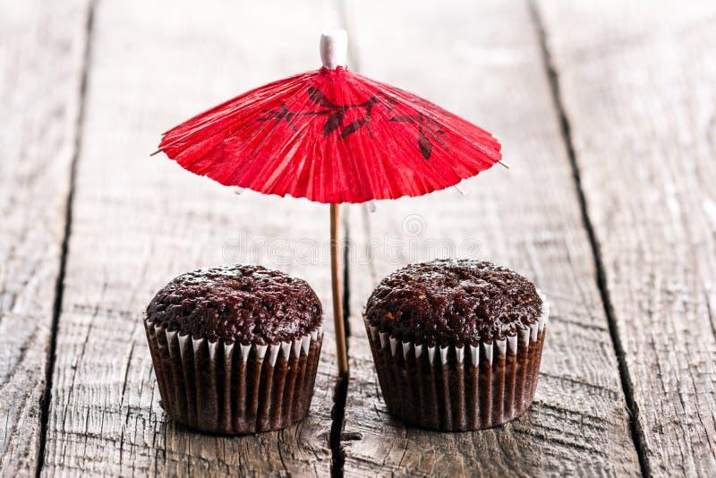 Muffins σοκολάτας κάτω από την κόκκινη ομπρέλα στοκ εικόνα