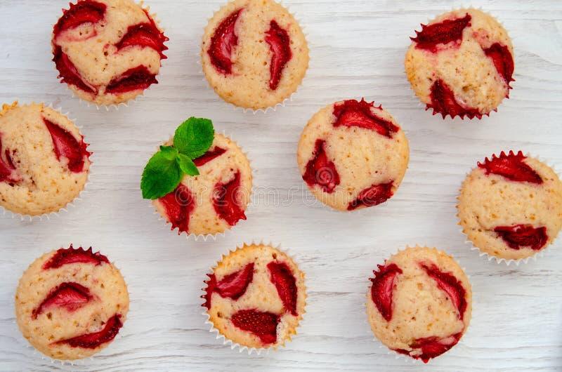 Muffins φραουλών, κλείνουν επάνω το άσπρο υπόβαθρο με τη μέντα στοκ φωτογραφία