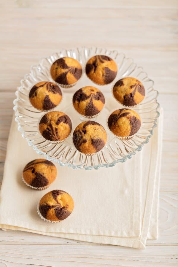 Muffins auf einer Platte auf hellem hölzernem Hintergrund stockbild