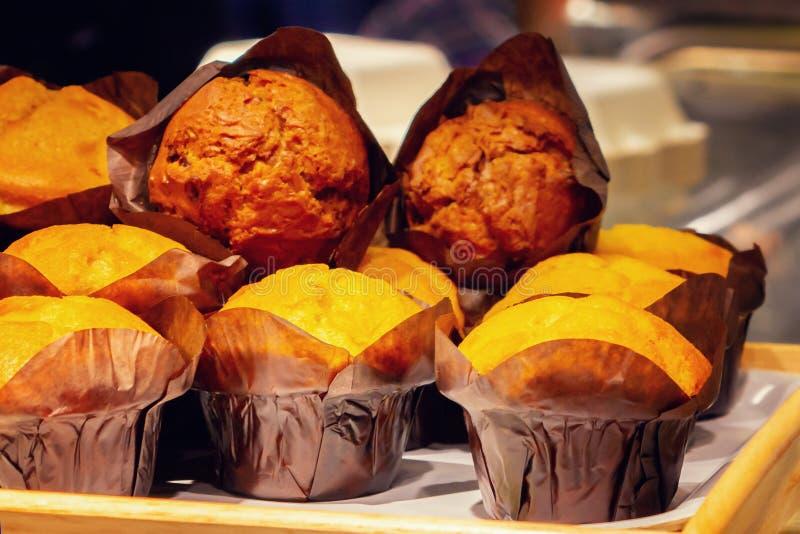 Muffins beim Papierverpacken ausgebreitet für Verkauf in einem Café lizenzfreie stockfotografie