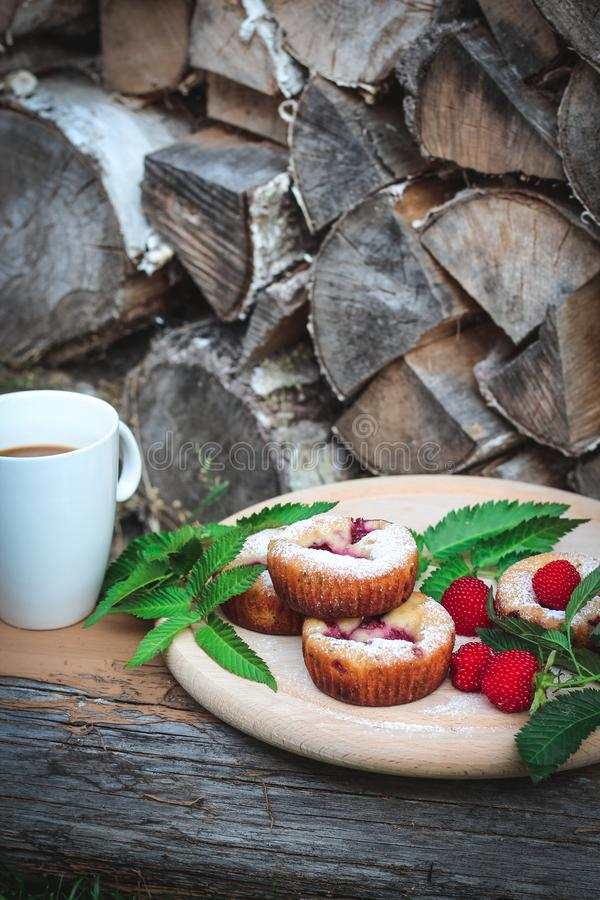 Muffins with berries and a cup of coffee served next to a firewood stack stock photo