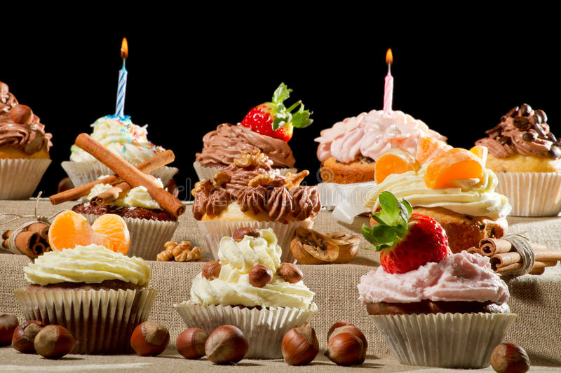 Muffins with cream, nuts and burning candles royalty free stock photo