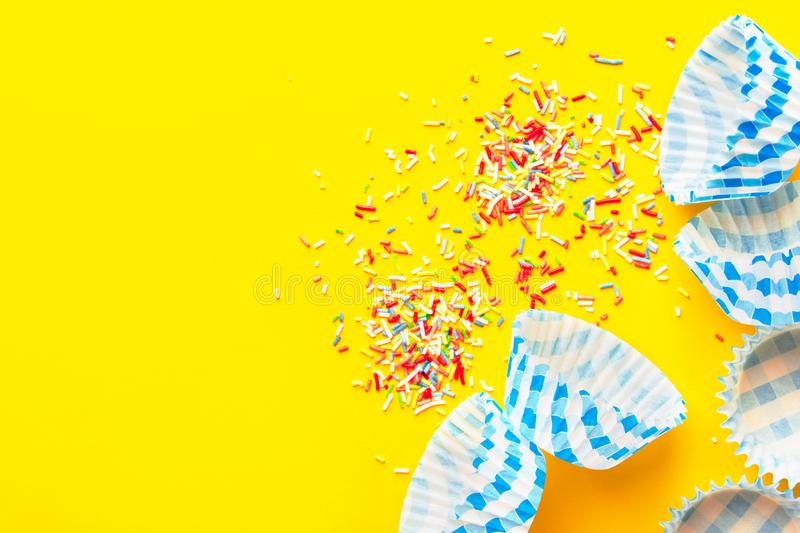 Muffins cupcakes paper cups liners multicolored rainbow sugar sprinkles on bright yellow background. Birthday party holiday baking royalty free stock images