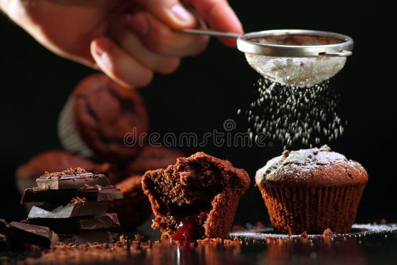Muffins die in gepoederde suiker gieten stock foto