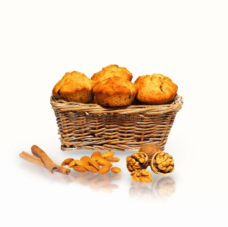 Muffins in einem Korb mit Nüssen, Mandeln und Zimt lizenzfreies stockfoto