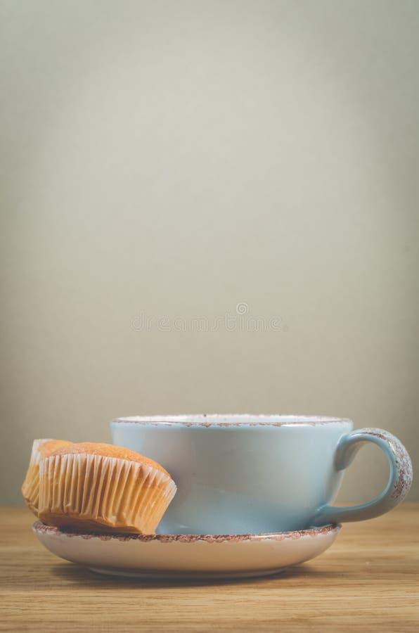 Muffins en blauwe mok met thee voor ontbijt, selectieve nadruk Achtergrond met exemplaarruimte stock afbeelding