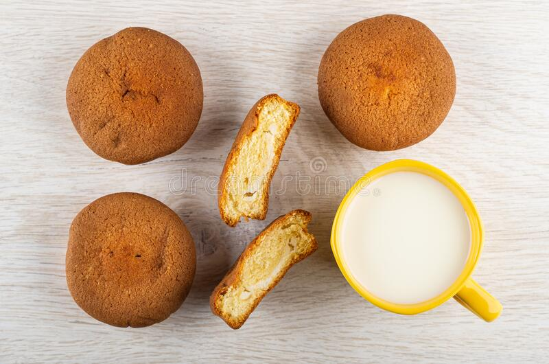 Muffins, halves of muffin, cup with milk, spoon on wooden table. Top view royalty free stock photos