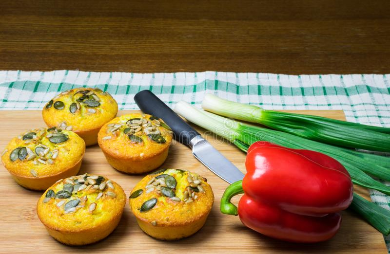 Few muffins made of corn flour with pumpkin and sunflower seeds, and red pepper, green onion and knife on wooden board. stock photo