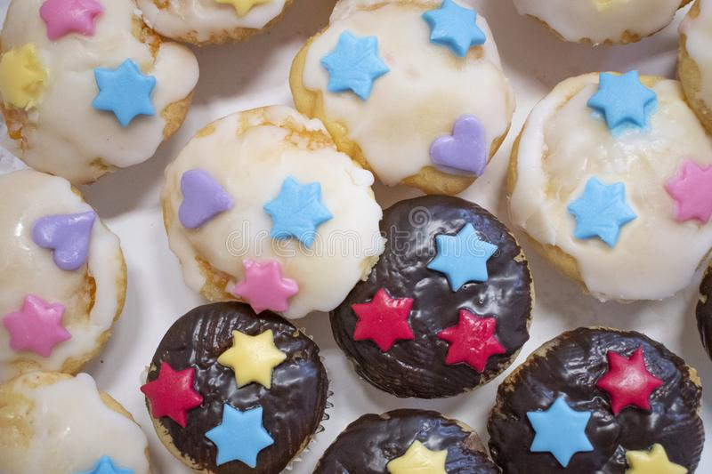 Muffins home made white and  black chocolate with collard stars and hearts. royalty free stock photos