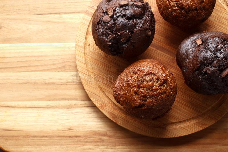 Muffins On Kitchen Boards. Raisin bran and chocolate chunk muffins on wooden kitchen boards. Above view stock photography