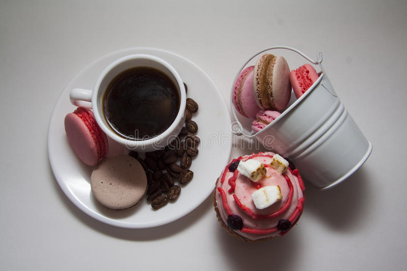 Muffins and maarons on coffee plate stock image
