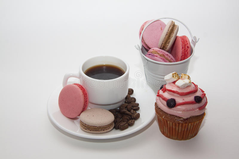 Muffins and maarons on coffee plate royalty free stock photo