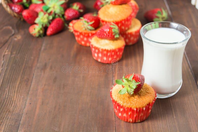 Muffins met aardbei en glas melk worden verfraaid die stock fotografie