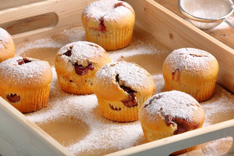 Muffins met jam die met gepoederde suiker op houten dienblad wordt bestrooid royalty-vrije stock fotografie