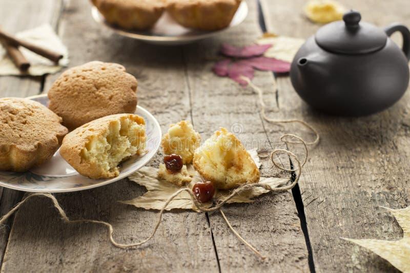 Muffins met jam op houten achtergrond Gietende jam op een cupcake stock afbeelding