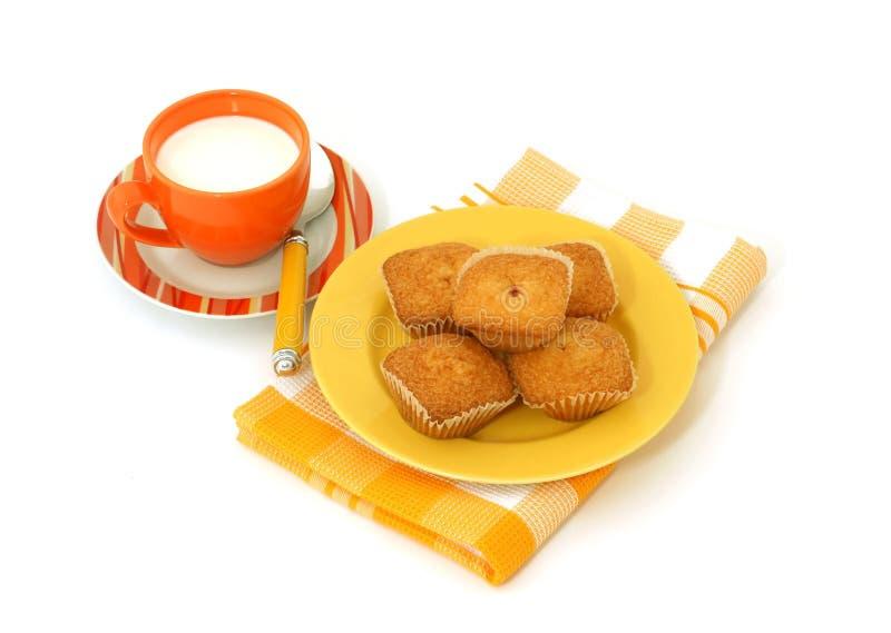 Muffins na talerzu i odizolowywająca dalej mleko filiżanka fotografia royalty free