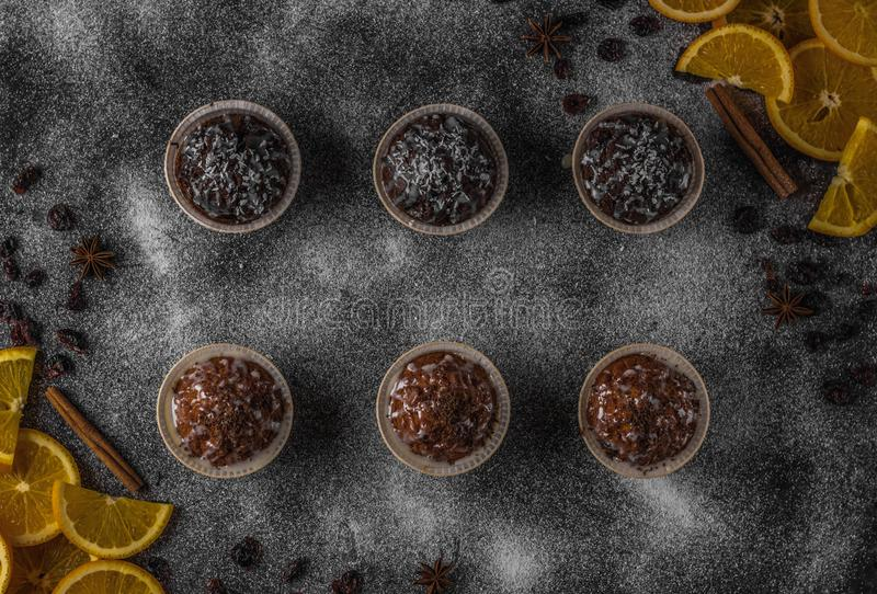 Muffins and oranges for dessert. Gray background from powdered sugar. View from above royalty free stock photography