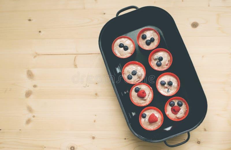 Muffins w czerwonych filiżankach przygotowywali dla baken w bakenform obrazy stock