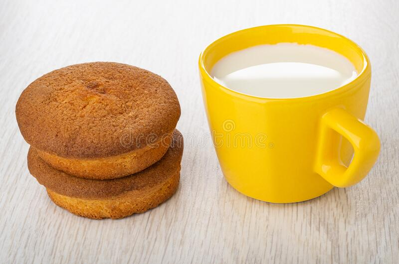 Muffins, cup with milk on wooden table stock photo