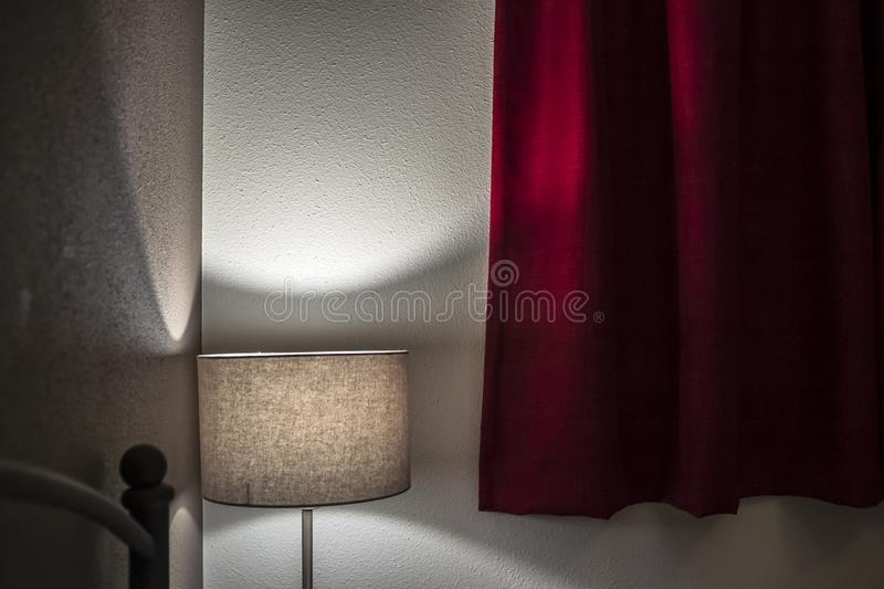 Muffled light from the floor lamp creates a relaxing, intimate atmosphere in the bedroom with thick red curtains royalty free stock image