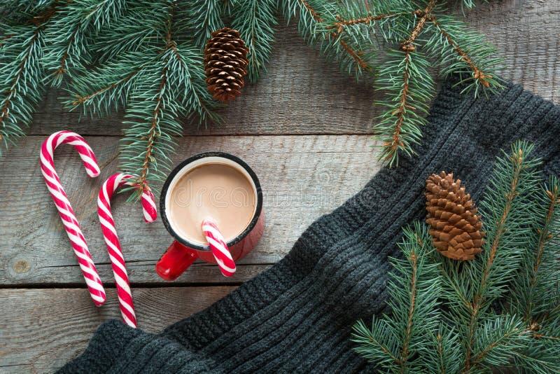 Mug горячий кофе с молоком, красной тросточкой конфеты на деревянной предпосылке с конусом, ветвью рождественской елки и серым ша стоковая фотография