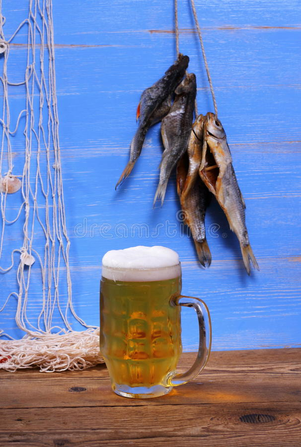 Mug of beer on blue background with dried rudd fish stock images