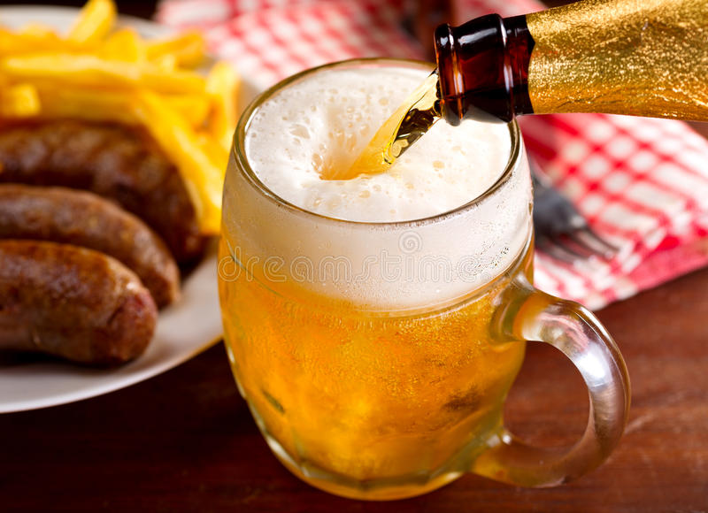 Mug of beer. Cold beer pouring into mug royalty free stock images