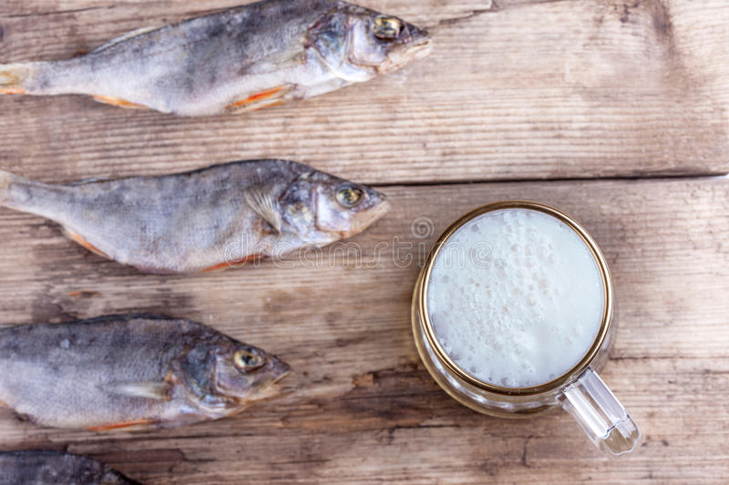 Mug of beer and dried fish on the table royalty free stock image