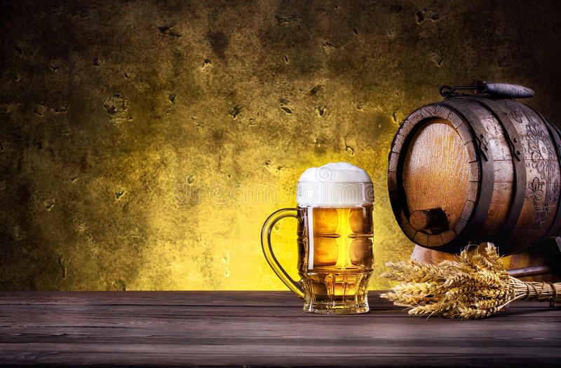 Mug of beer with foam and barrel royalty free stock images